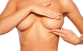 Naked female holding her breast after breast surgery in Manchester